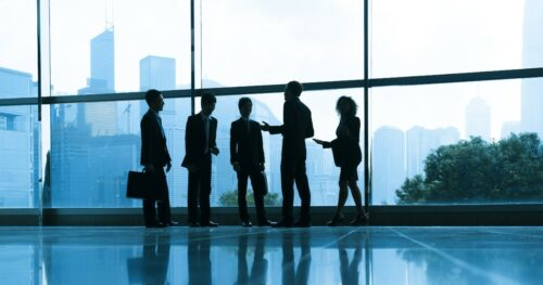 A group of business people standing in a halllway and talking.
