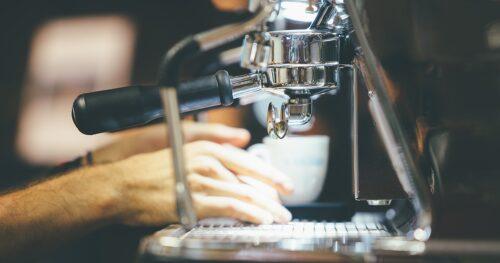 A barista putting a coffee cup under a coffee machine's portafilter.