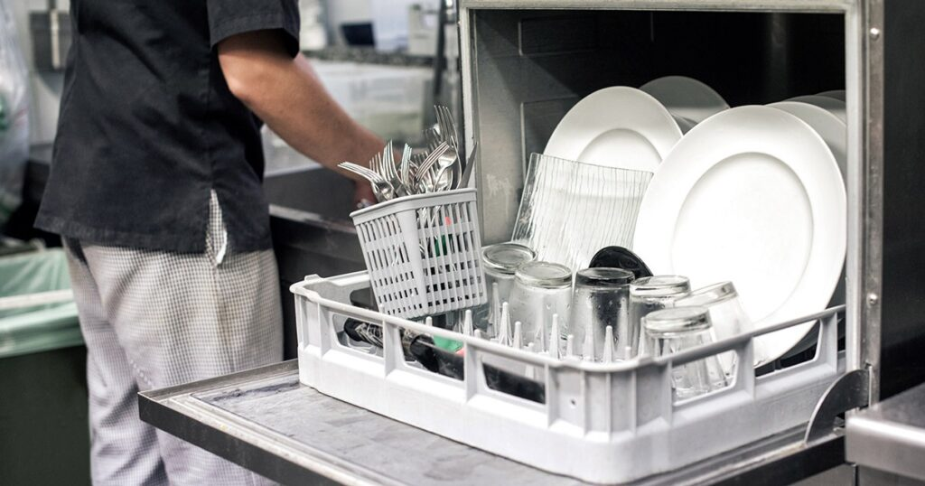 A man standing next to a opened dishwasher in a restaurant kitchen.